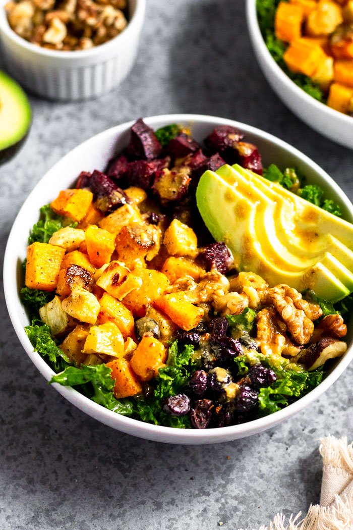 Winter power salad with roasted squash, parsnips, and beets, avocado, nuts, and dried fruit. It is topped with a vegan tahini dressing. Behind it is another bowl, dish of walnuts, and half an avocado.