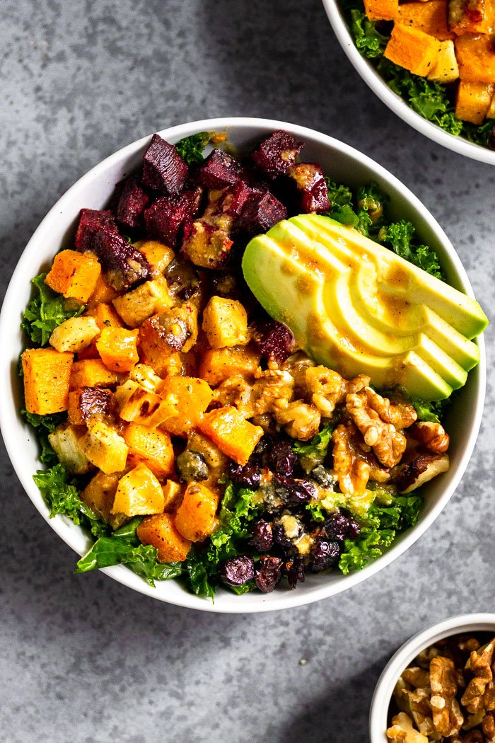 Vegan power bowl filled with butternut squash, parsnips, beets, kale, avocado, walnuts, and dried cranberries and topped with a tahini dressing. Next to is is another bowl and small dish of walnuts.