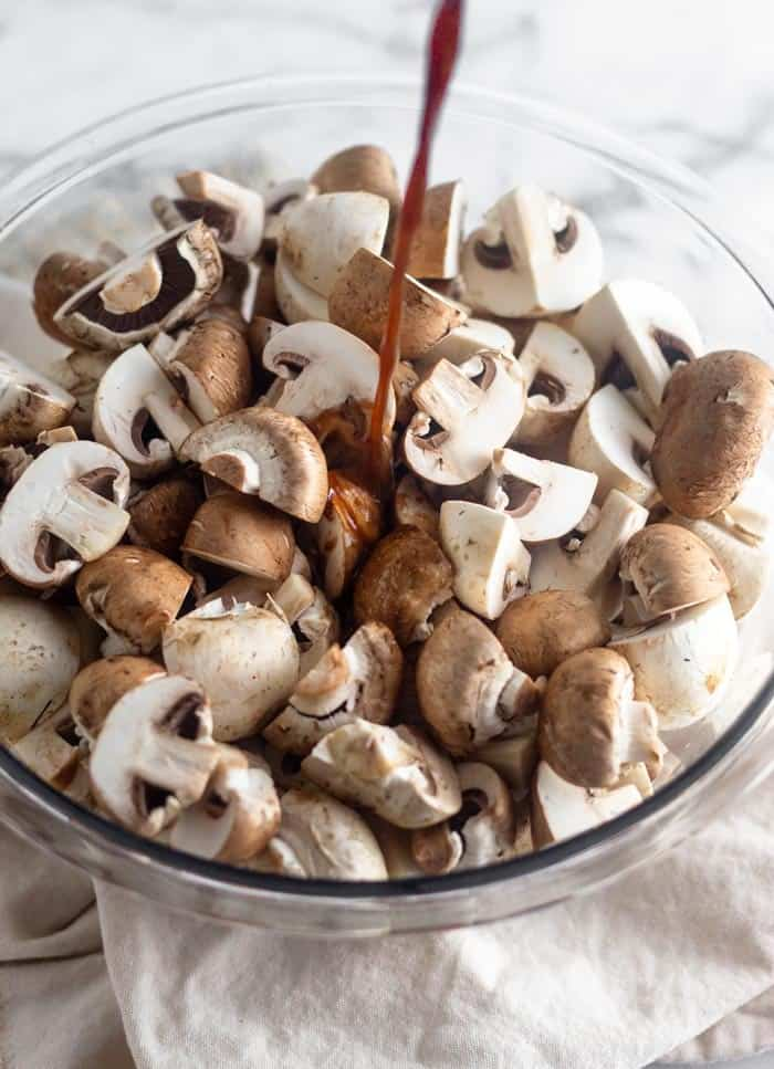 A glass bowl of mushrooms with a balsamic dressing being poured on them