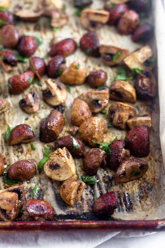 Sheet pan of balsamic roasted mushrooms with leaves of parsley sprinkled on them