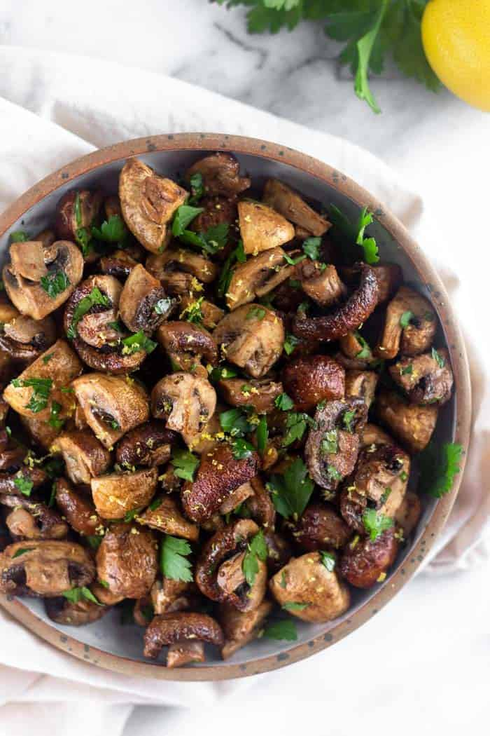 Overhead view of a bowl filled with balsamic roasted mushrooms topped with fresh parsley and lemon zest