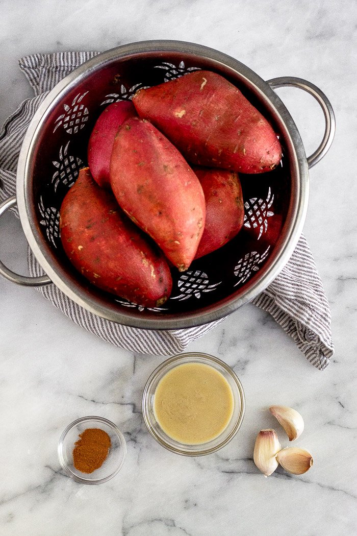 White counter top with sweet potatoes in a colander on a towel, a bowl of tahini, a bowl of cinnamon, and 3 cloves of garlic.