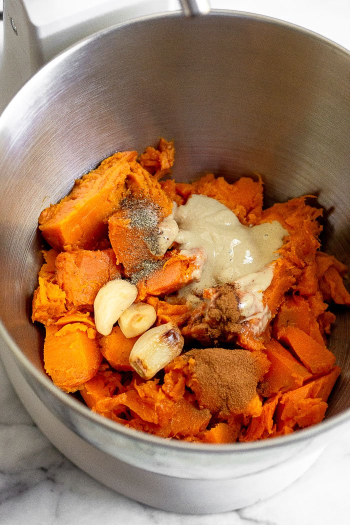 Stand mixer bowl willed with roughly chopped up cooked sweet potatoes, tahini, roasted garlic, cinnamon, and salt and pepper.