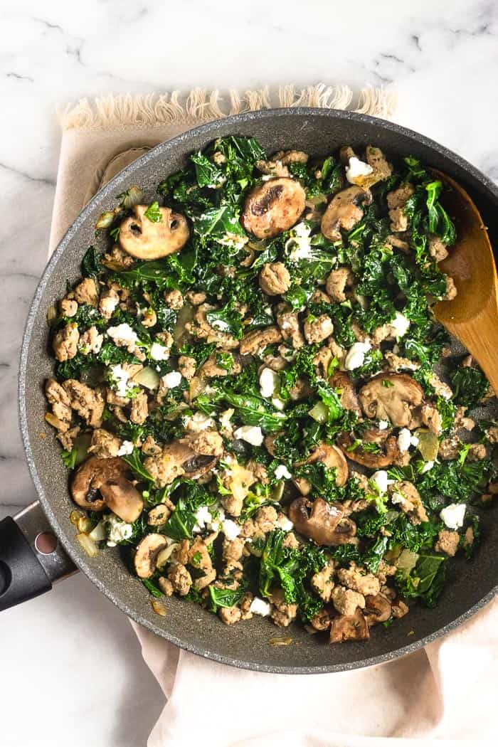 A large skillet filled with cooked ground turkey, kale, mushrooms, onion, and goat cheese going to used as the filling for spaghetti squash with ground turkey.