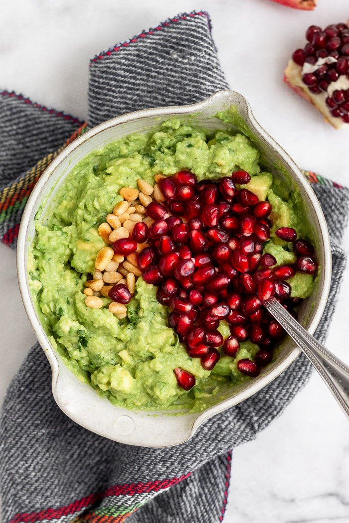Small bowl filled with smashed avocado, toasted pine nuts, and pomegranate arils.