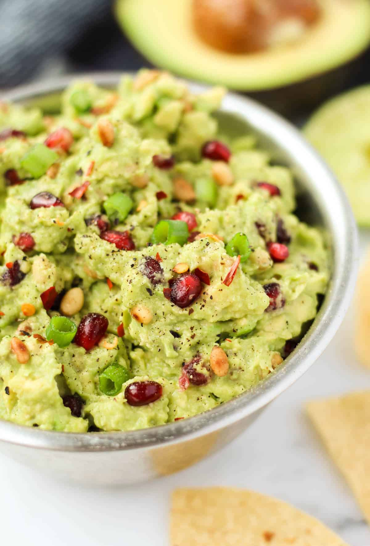 An easy and festive appetizer, this Pomegranate Guacamole comes together in 5 minutes and is vegan, paleo, dairy and gluten free, and Whole30 compliant - Eat the Gains