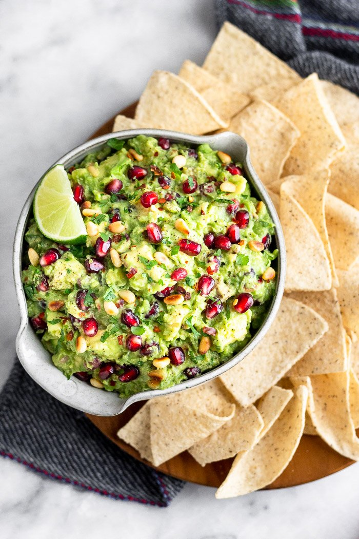 A bowl filled with pomegranate guacamole with chips surrounding it on a wooden plate. The plate is on a blue linen.