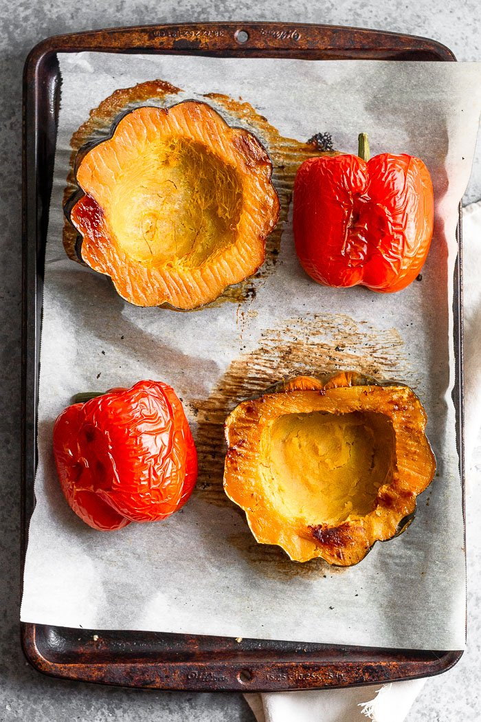 Baking sheet lined with parchment paper with 2 halves of roasted acorn squash and 2 roasted red peppers.