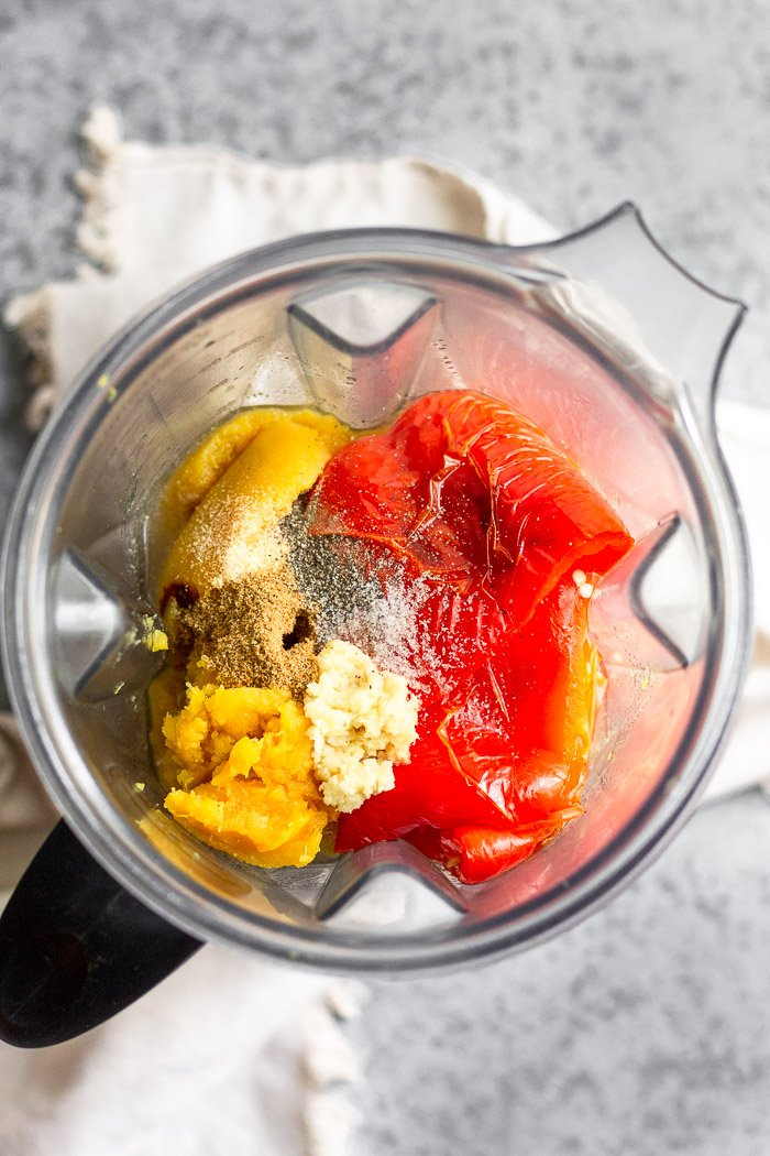 Blender filled with broth, roasted squash and red peppers, fresh grated ginger, and spices.