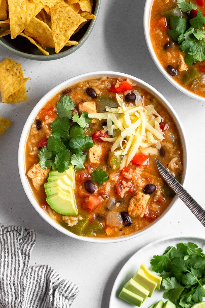 Bowl of chicken fajita soup topped with avocado, cilantro, and shredded cheese. Around it is another bowl of soup, a bowl of chips with a few laying next to it, a striped kitchen towel, and a plate of avocado and cilantro.