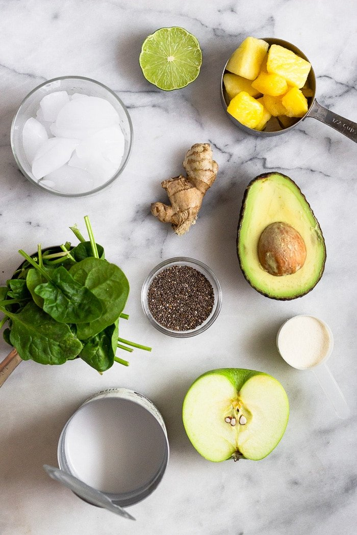 Overhead shot of a white counter with a bowl of pineapple, ginger root, bowl of chia seeds, half an avocado, protein powder, half a green apple, can of coconut milk, cup of spinach, and glass of ice.