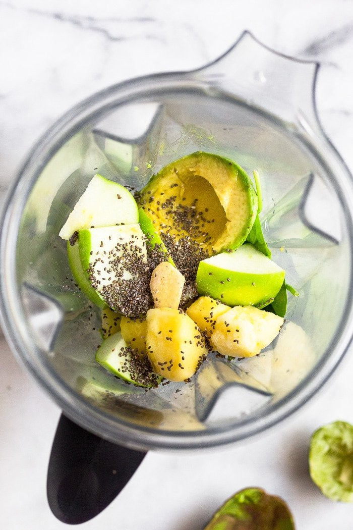 Overhead shot of a Vitamix filled with apple, pineapple, avocado, chia seeds, and ginger.