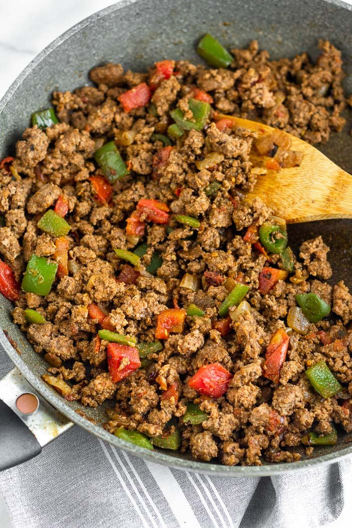 A large skillet filled with cooked taco meat with a wooden spoon coming out of it.