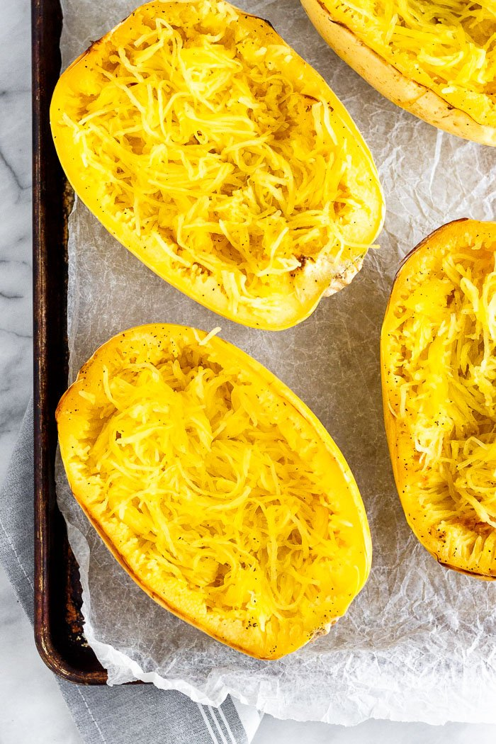 A large baking sheet with halves of cooked spaghetti squash on it.