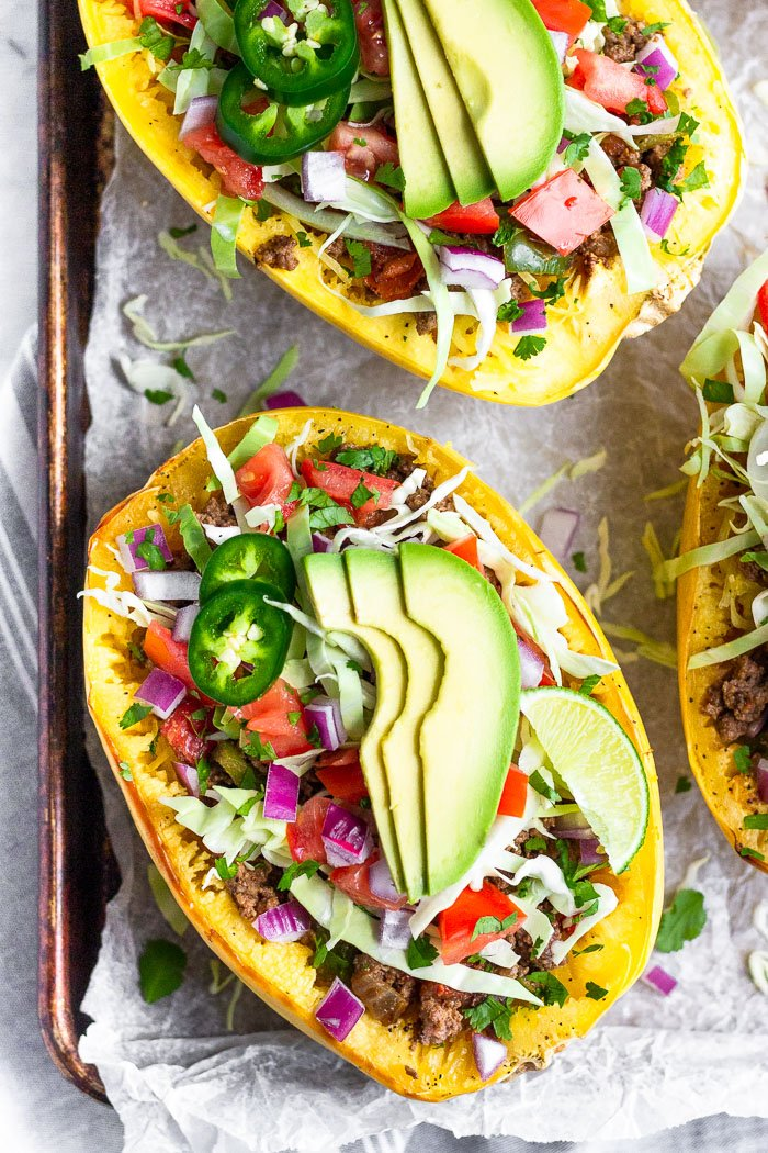 Overhead shot of 3 taco spaghetti squash boats topped with cabbage, tomatoes, onion, avocado, and jalapeños on a baking sheet .
