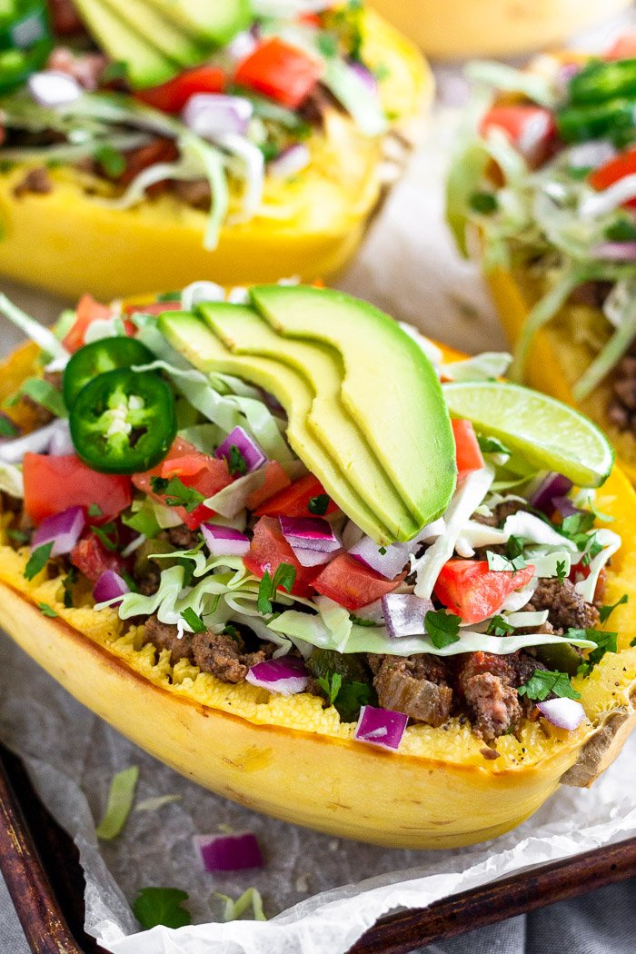 A baking tray with taco stuffed spaghetti squash boats on top that are topped with cabbage, diced tomatoes, avocado, cilantro, and jalapeños.