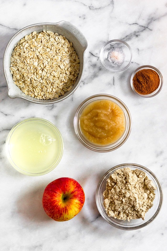 White counter filled with an apple and individual bowls of oats, salt, cinnamon, apple sauce, protein powder, and egg whites.