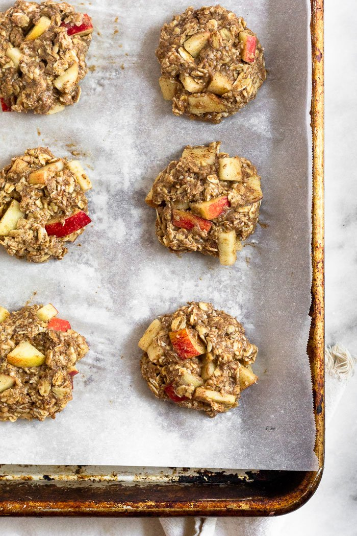Baking sheet lined with parchment paper filled with apple cinnamon protein cookies before they are baked.