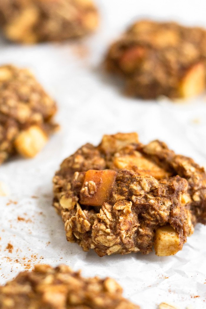 Apple Cinnamon Protein Cookies on a white surface with cinnamon and oats sprinkled around them.
