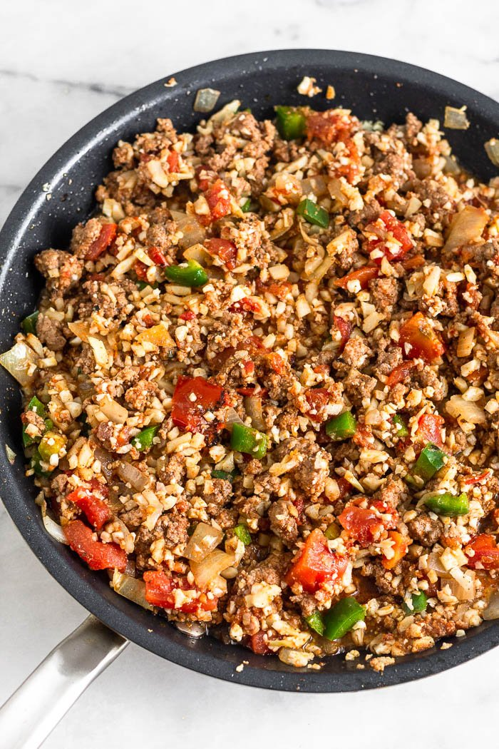Pan filled with cooked ground beef, cauliflower rice, onion, jalapeno, canned tomatoes, and spices.