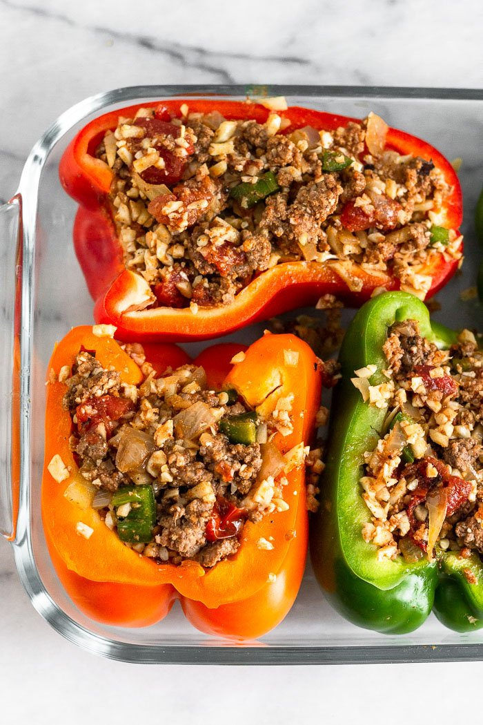 Glass baking dish filled with beef stuffed peppers before they are baked.