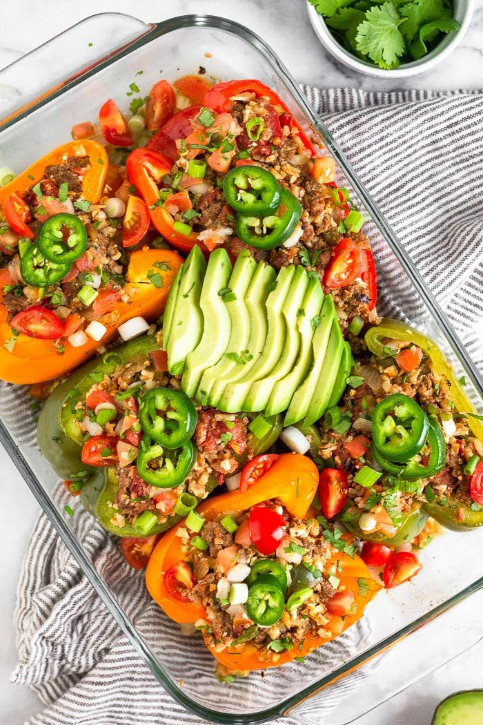 Overhead shot of a glass baking dish filled with stuffed peppers with ground beef and rice. They are topped with sliced avocado, jalapeno, cilantro, and green onion. The pan is sitting on a striped towel with a small dish of cilantro next to it.