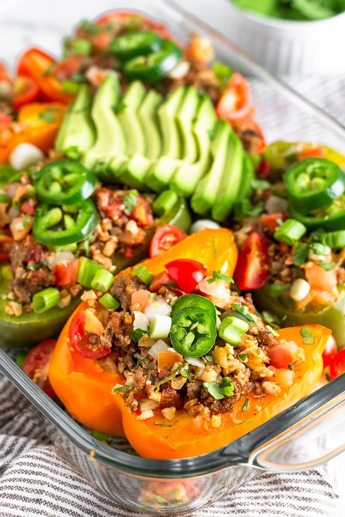 Baking dish filled with Whole30 stuffed peppers with beef and cauliflower rice. They are topped with avocado, jalapeno, cilantro, diced tomatoes, and green onion. The dish is sitting on a striped towel.