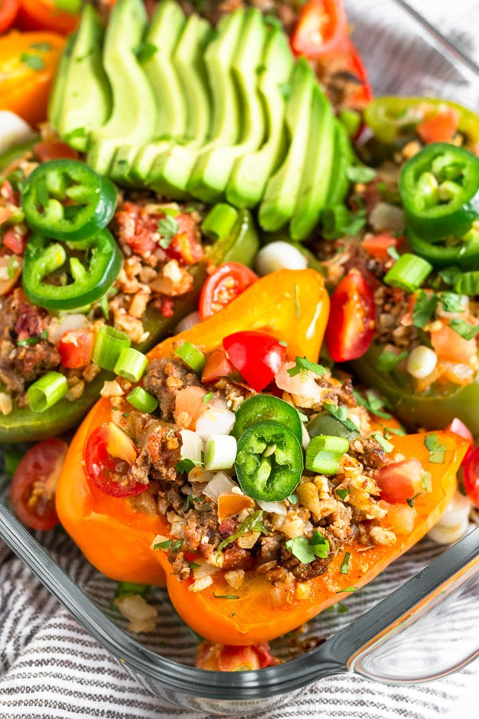 Glass dish filled with beef and rice stuffed peppers topped with sliced jalapeno, green onion, diced tomatoes, cilantro, and sliced avocado.