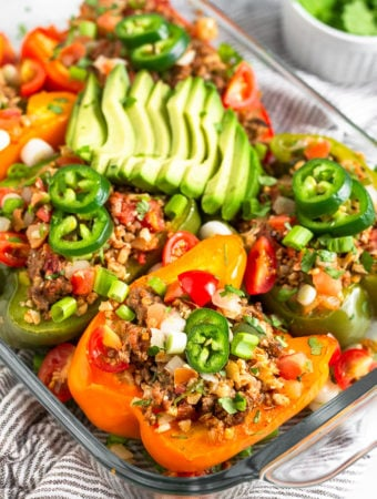 Baking dish filled with Whole30 stuffed peppers with beef and cauliflower rice. They are topped with avocado, jalapeno, cilantro, and green onion. Behind the dish is a small dish of cilantro.