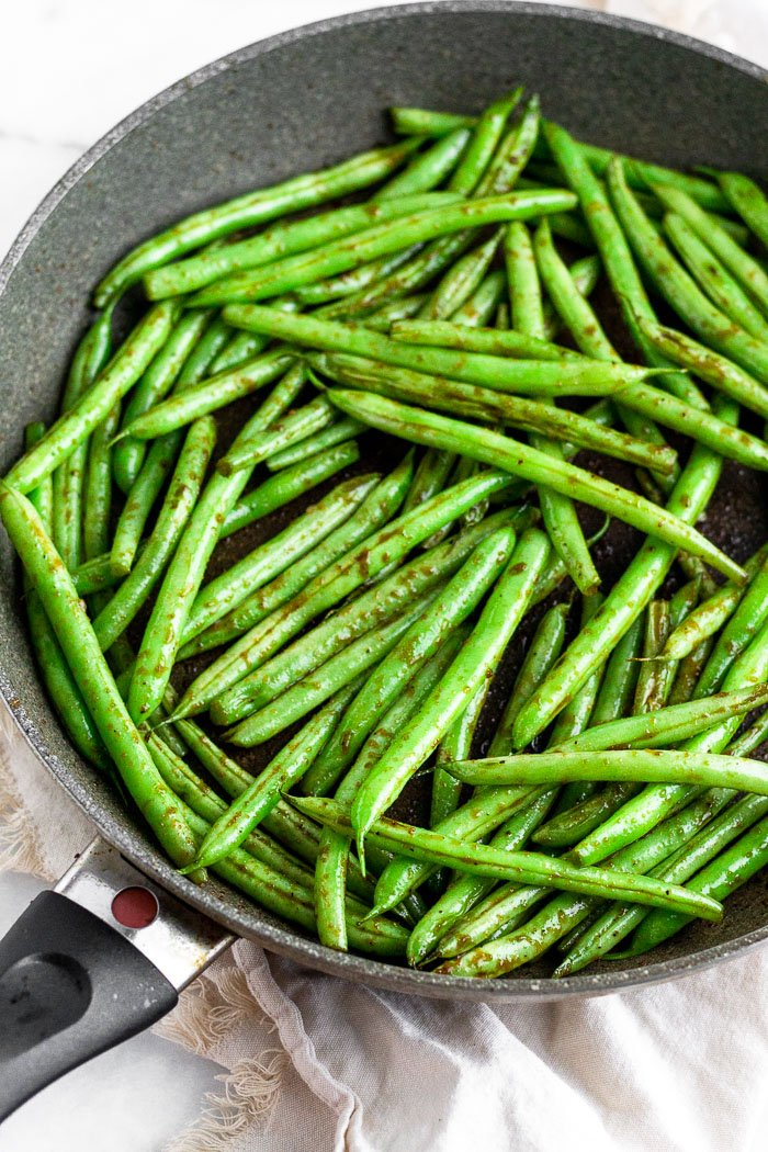 Large sauté pan filled with sesame garlic green beans sitting on a tan linen.