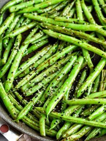 A close up of a large sauté pan filled with sesame garlic green beans.