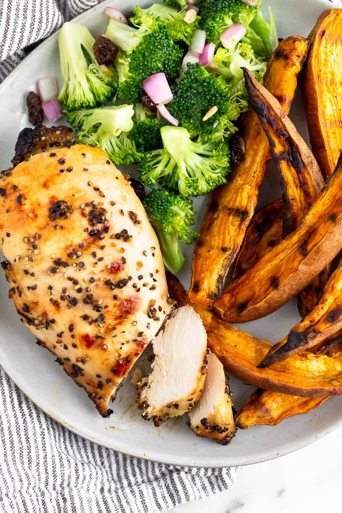 Plate filled with a piece of grilled lemon chicken that has 2 pieces cut from it. Next to it are grilled sweet potato fries and a broccoli salad.