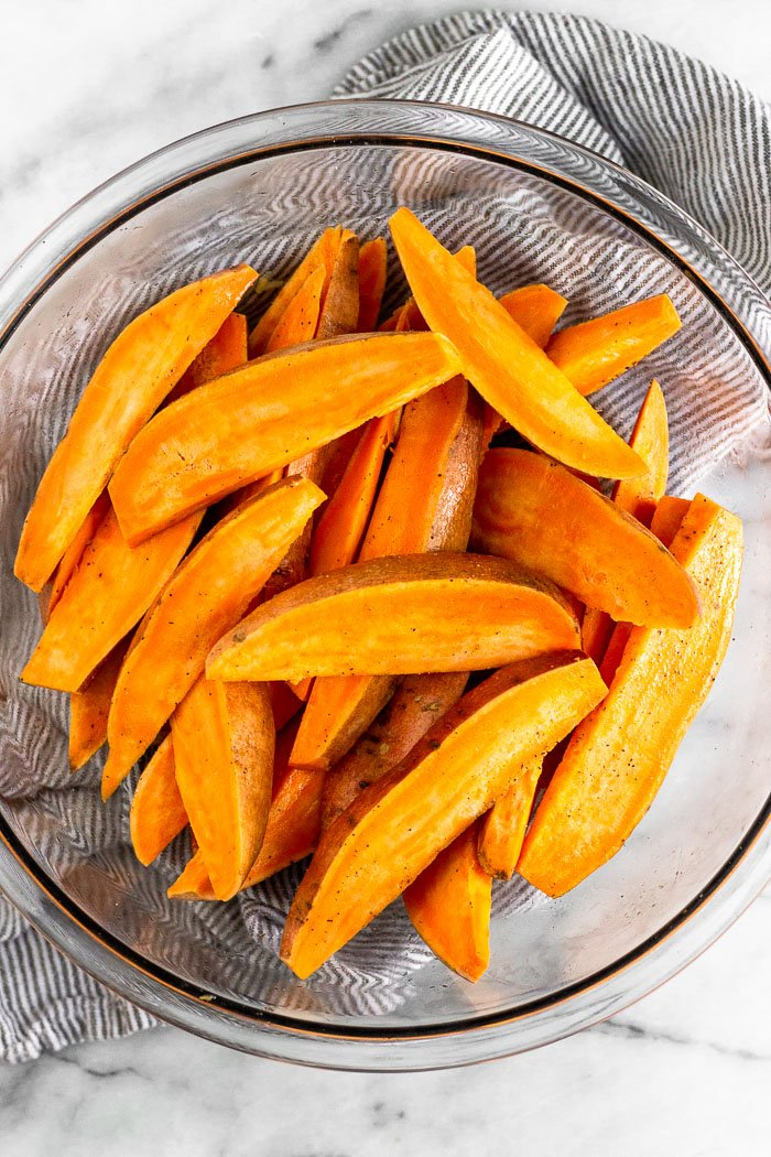 Glass bowl full of sweet potato wedges.
