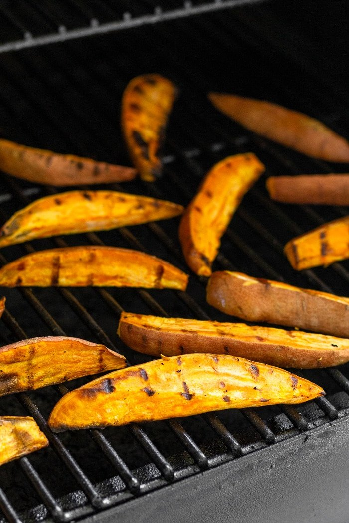 Sweet potatoes wedges cooking on the grill