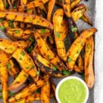 Baking sheet with grilled sweet potato fries topped with fresh parsley an a green dipping sauce.