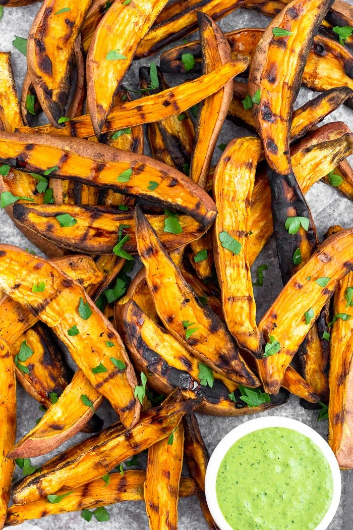 Close up of a bunch of grilled sweet potato wedge fries topped with fresh chopped parley and a green tahini dipping sauce in a small saucer next to them.