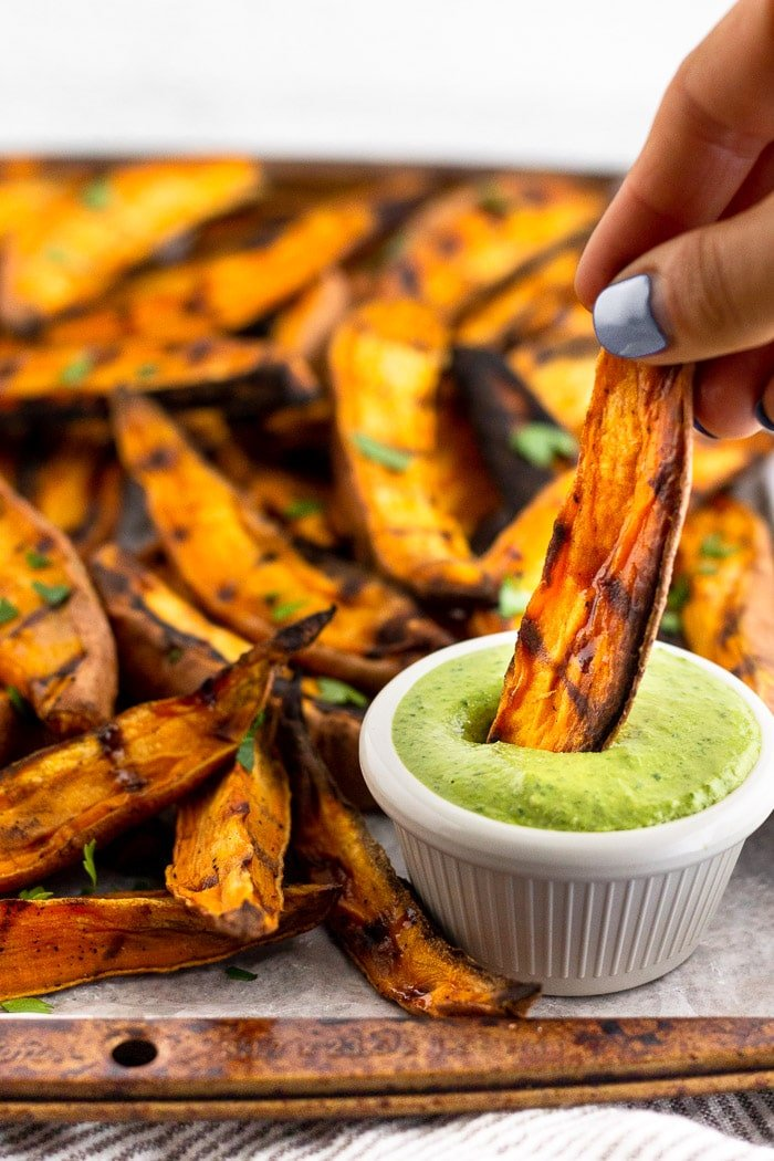 Large sweet of sweet potato wedges with someone holding one and dipping it into a small saucer of green sauce.