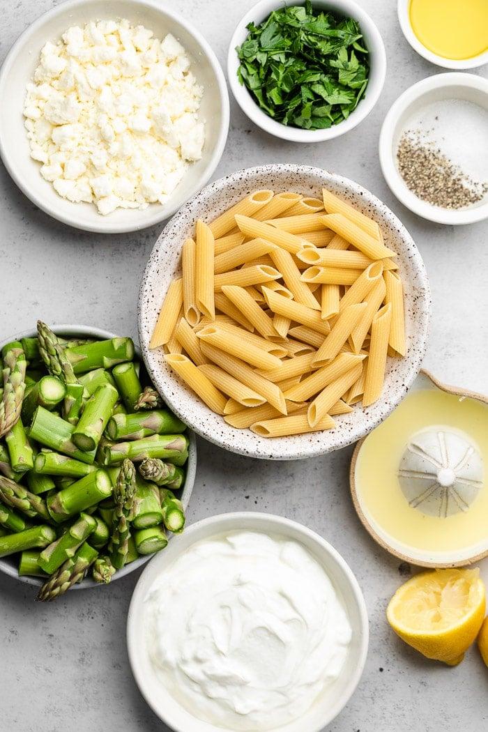 Overhead shot of a bowl of feta, bowl of herbs, bowl of pasta, lemon juice, bowl of greek yogurt, and a bowl of asparagus.