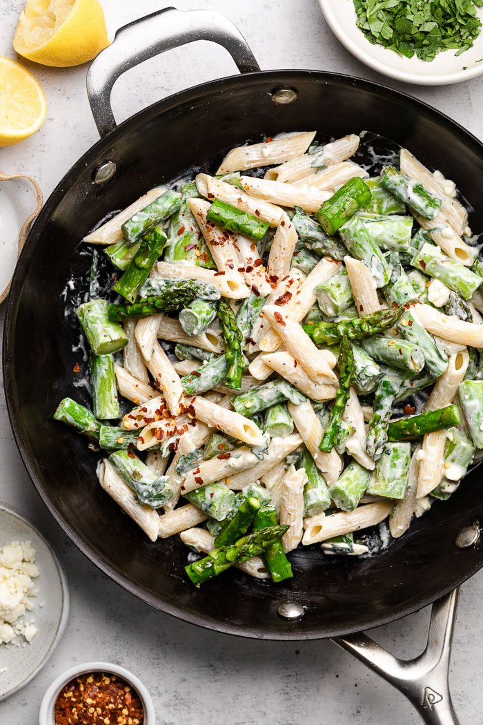 Pasta with asparagus and lemon in a pan topped with red pepper flakes. Around the pan is a small bowl or red pepper flakes, lemons, bowl of feta, and a bowl of fresh herbs.