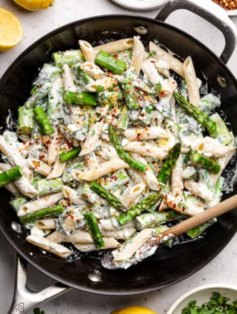 Pan of lemon asparagus pasta with creamy feta sauce topped with red pepper flakes. Around the pan is some lemons, herbs, and spices.