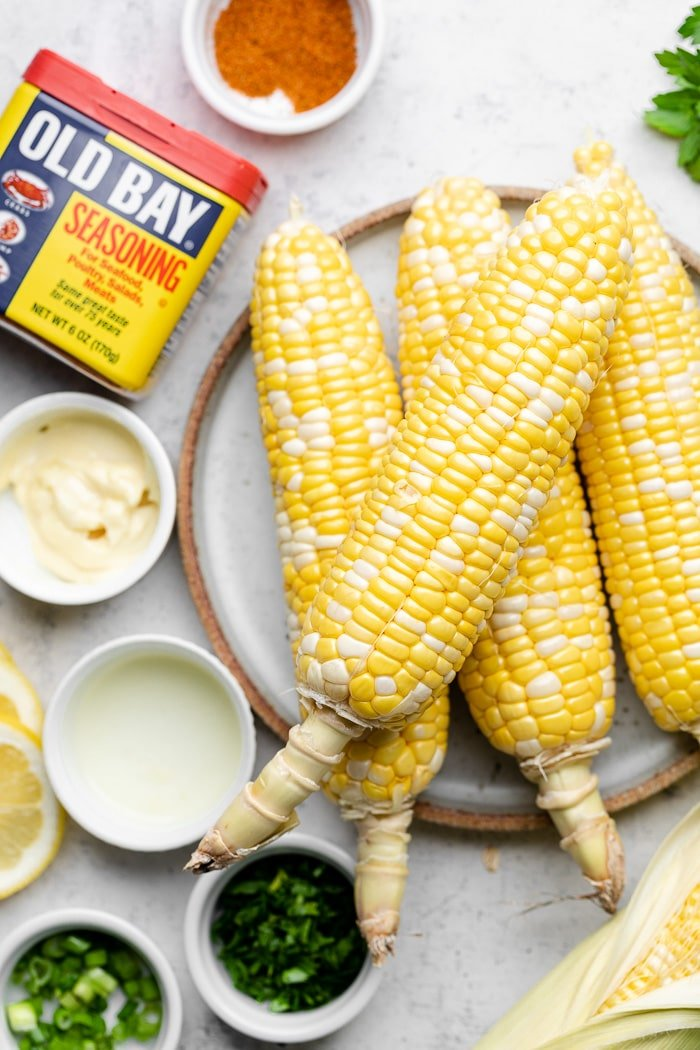Overhead shot of husked corn on the cob, small bowls of herbs, bowl of mayo, and and Old Bay container with it in a bowl next to it.