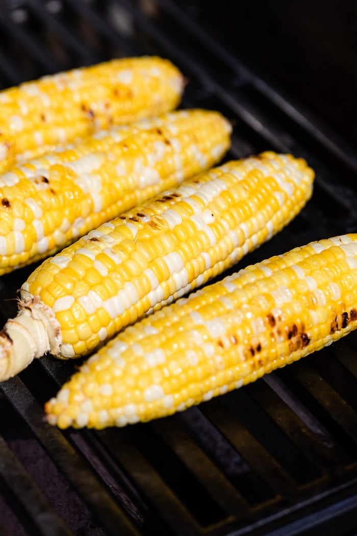 Four pieces of corn on the cob on the grill cooking.