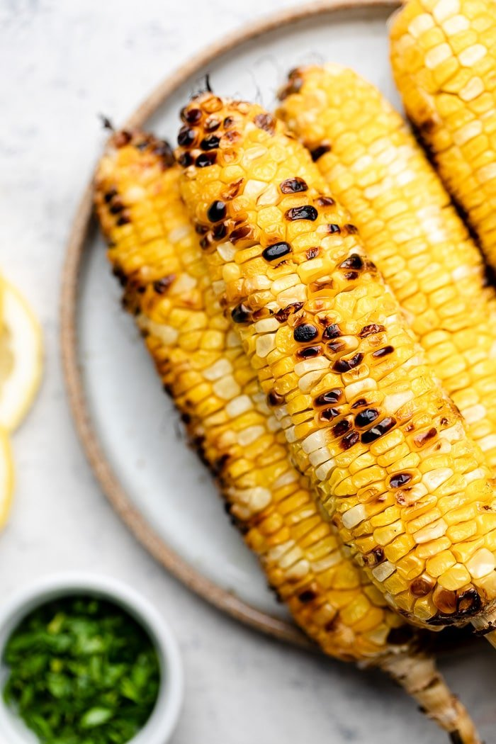 Plate with a stack of grilled corn on the cob on it. Next to it is a small bowl of herbs.