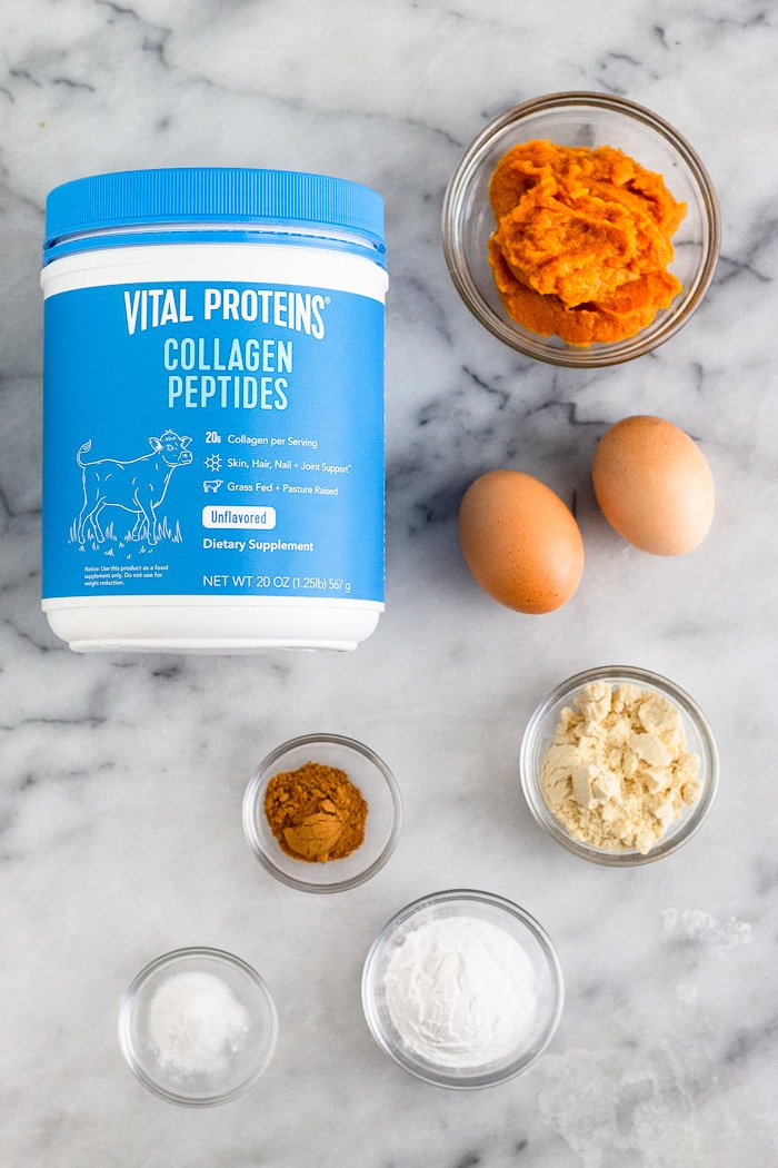 White counter with a blue container of collagen, bowl of pumpkin puree, 2 eggs, bowl of coconut flour, bowl of tapioca flour, bowl of baking soda, and bowl of spices.