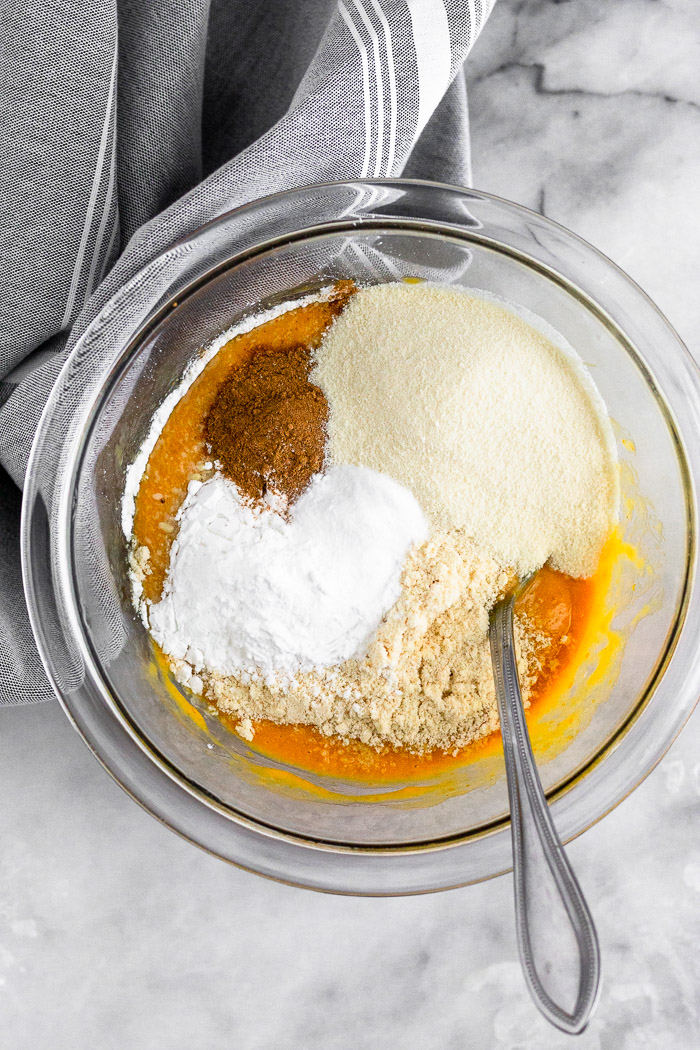 Glass bowl with pumpkin puree, eggs, flour, spices, baking soda, and protein powder in it. A fork is sticking out of it.