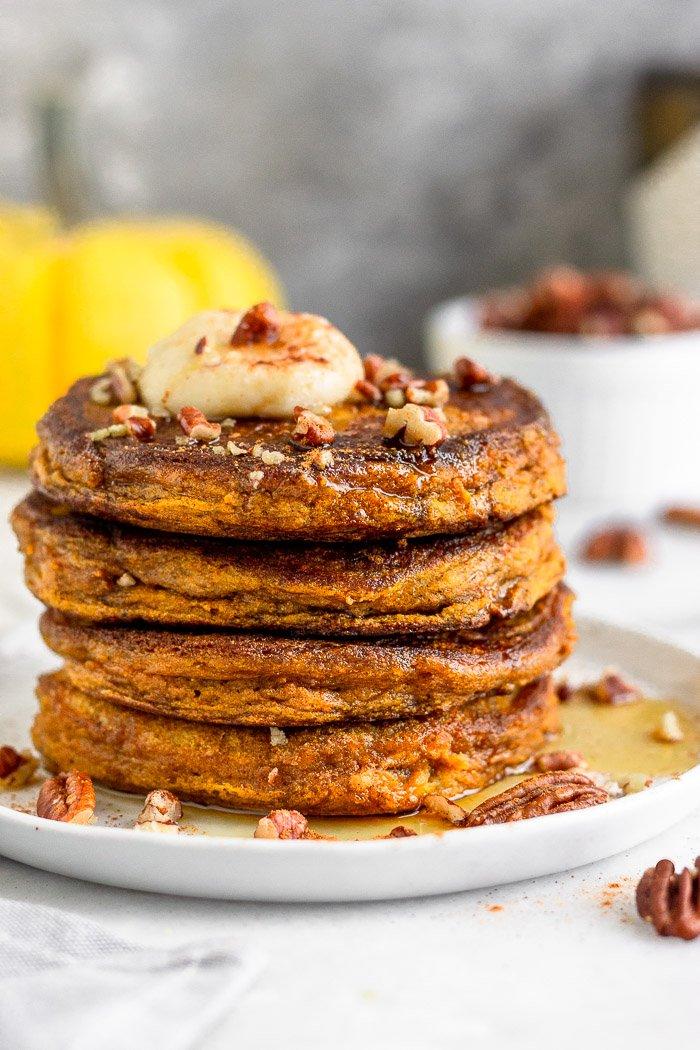 Stack of gluten free pumpkin protein pancakes sitting on a white plate. The pancakes are topped with coconut butter and chopped nuts and there is syrup all over the plate. Behind it is a yellow pumpkin and a small dish of nuts.