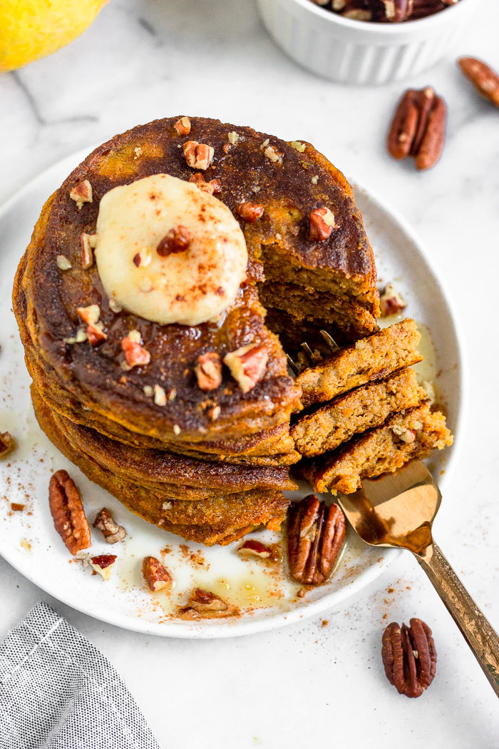 Overhead view of a stack of pumpkin pancakes with protein topped with coconut butter, chopped pecans, and maple syrup. A slices is missing from the stack and is on a fork that is laying on the plate.