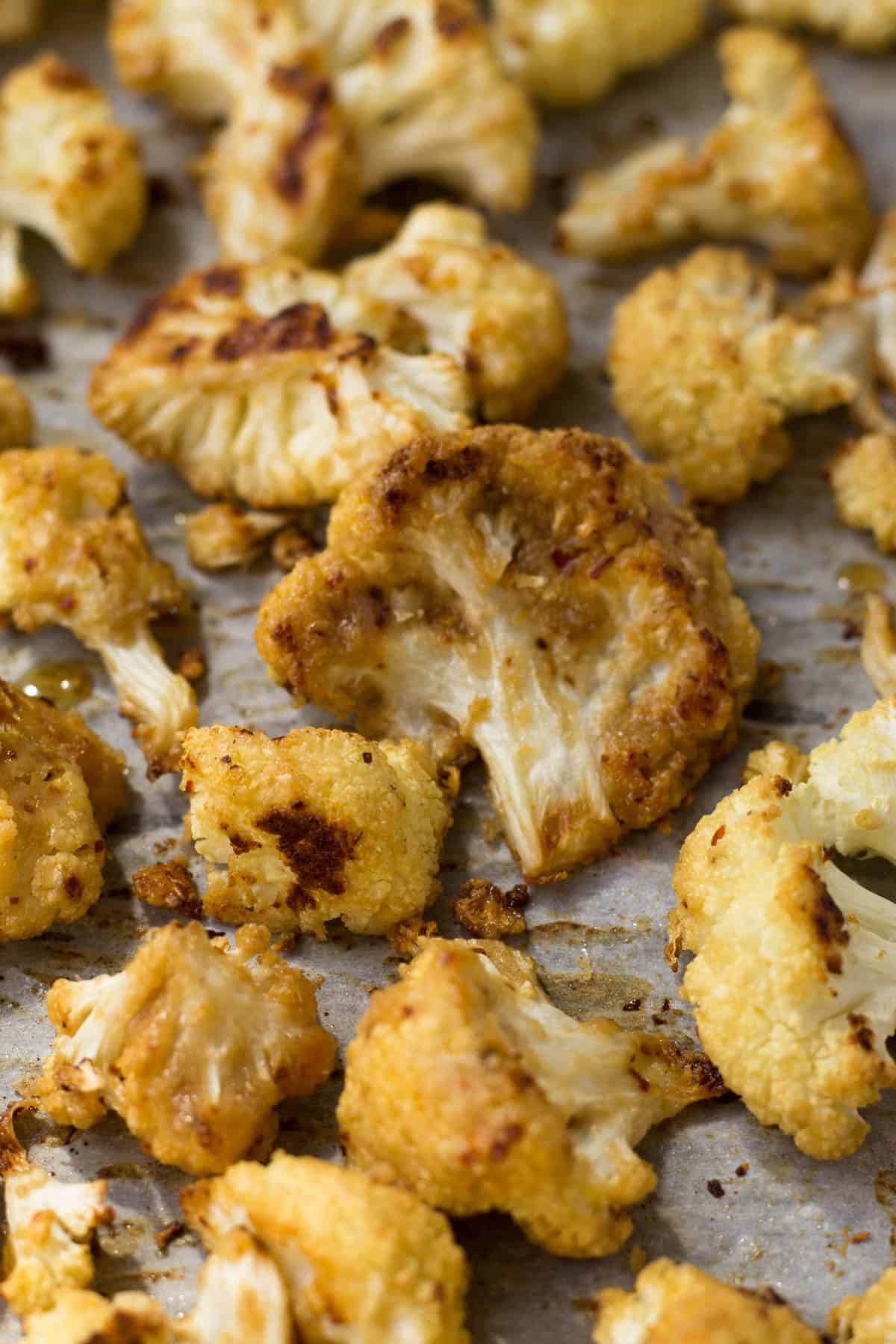 This vegan and paleo Maple Tahini Roasted Cauliflower make for an easy sweet and savory side dish - Eat the Gains