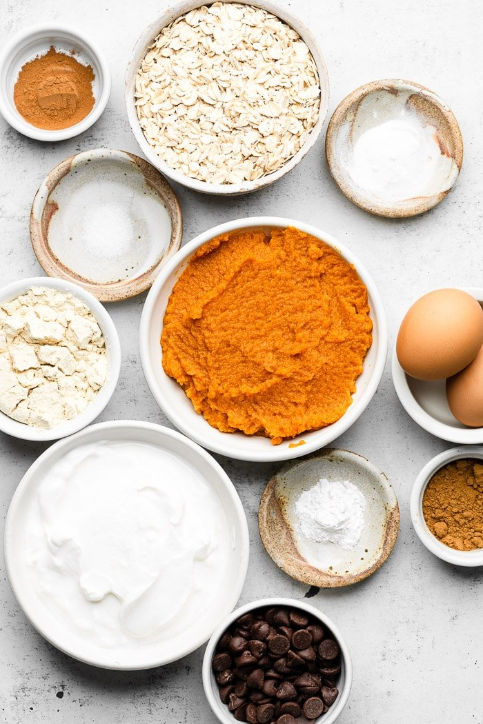 White counter filled with a bowl of spices, bowl of rolled oats, bowl of baking soda and powder, bowl of eggs, bowl of pumpkin puree, bowl of greek yogurt, and a bowl of protein powder.