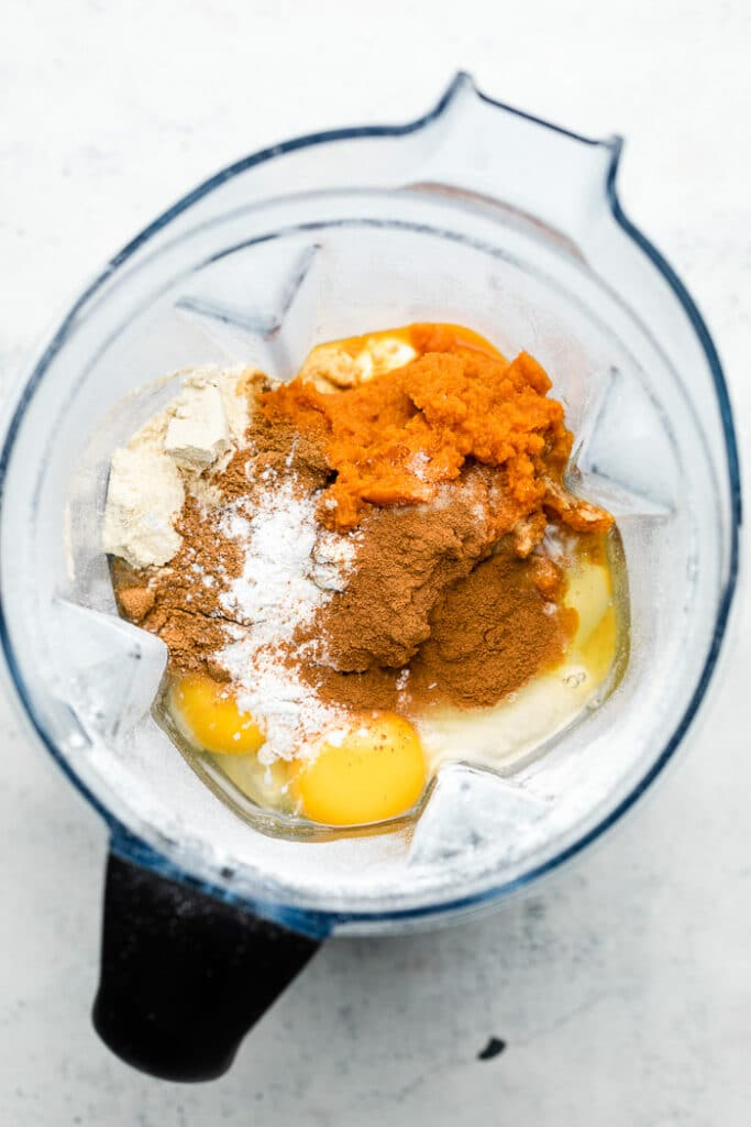 Blender filled with oats, eggs, pumpkin puree, spices, and baking soda and powder.